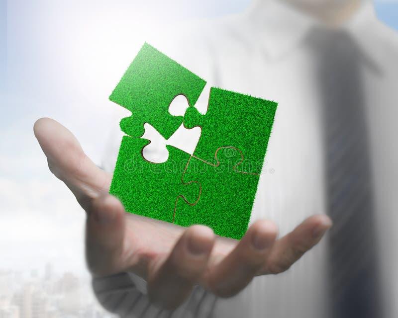 Otwarta męska ręka z zieloną trawą wyrzynarek łamigłówki obraz stock