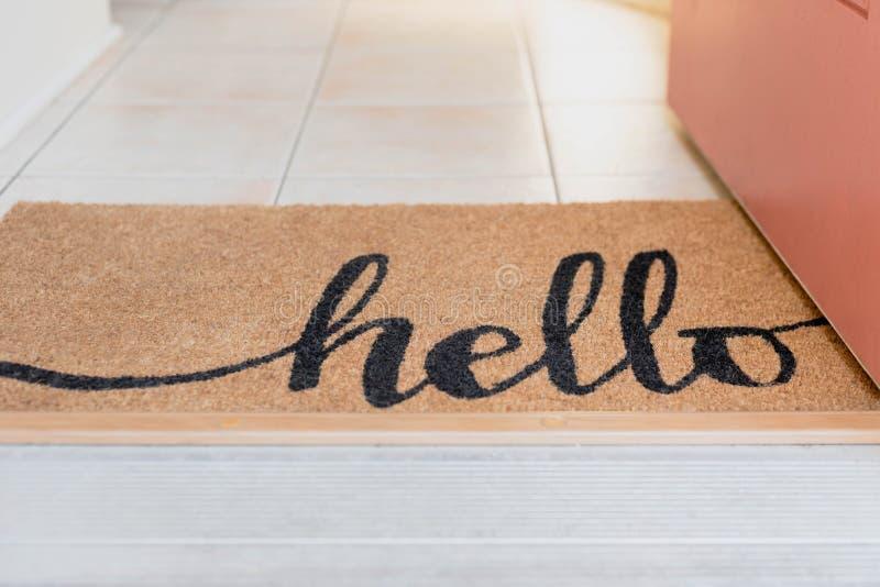 Otwarte drzwi z naturalnego włókna dywanikiem z słowem pisać i cześć fotografia stock