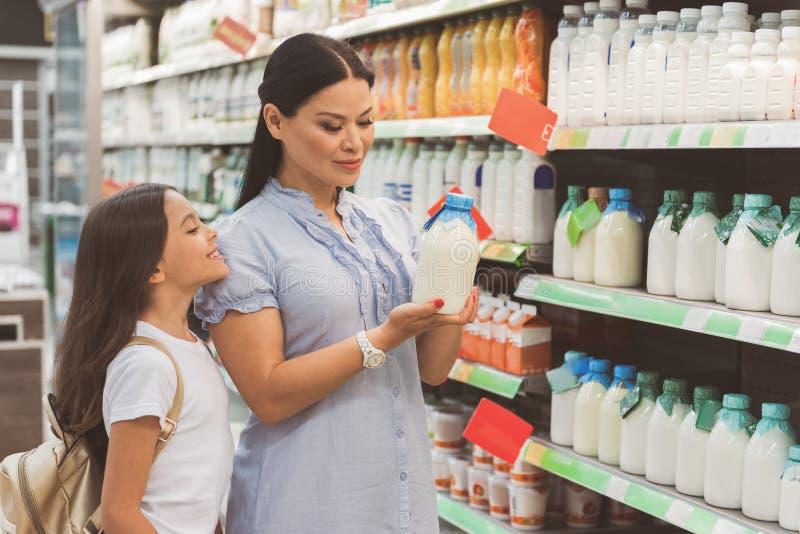 Otwarty dziecka i damy dopatrywanie przy mlekiem obraz royalty free