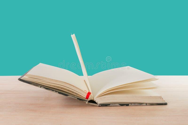 Otwarty książkowy stary na drewnianej podłoga odizolowywającej na błękitnym tle z kopii przestrzenią dodaje tekst zdjęcie royalty free