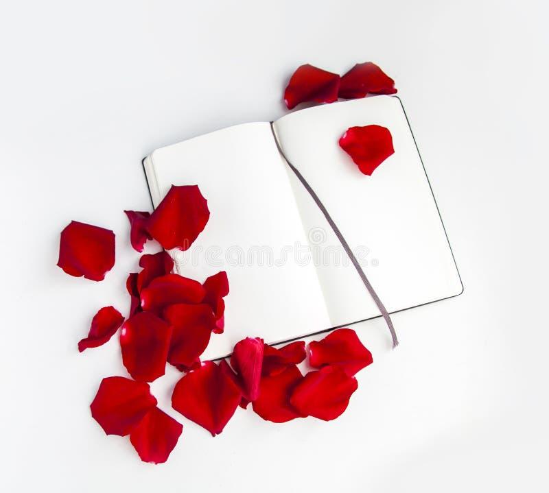 Otwarty notatnik i czerwone płatki róży obraz stock