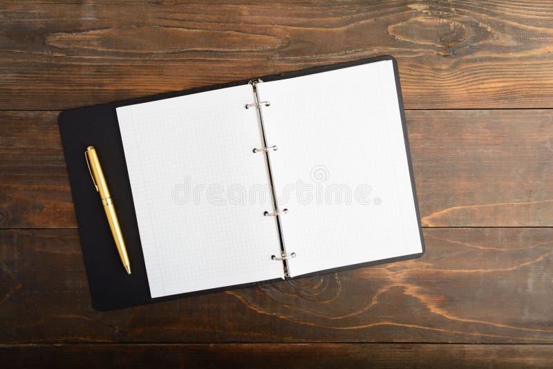 Otwarty notatnik i złoty pióro nad drewnianym stołem z kopii przestrzenią zdjęcia royalty free