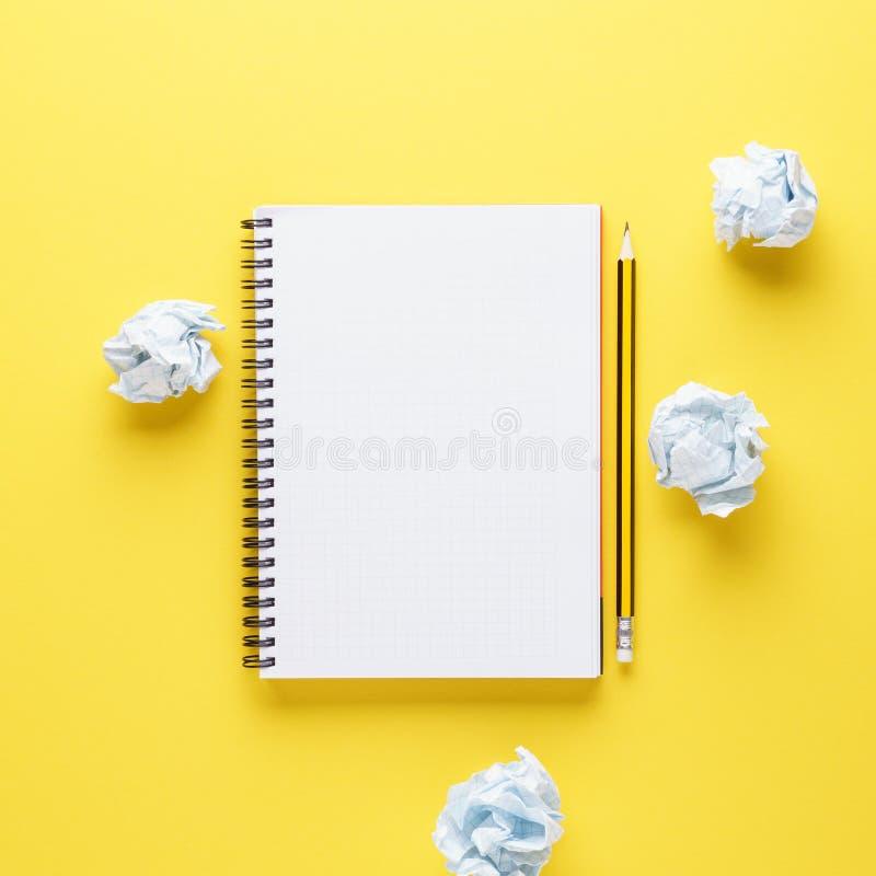Otwarty notatnik, ołówek i miący papiery na żółtym tle, obrazy stock