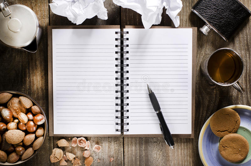 Otwarty notatnik z pustymi stronami, pióro na drewno stole Filiżanka herbata, modna kolba, dokrętki i ciastka, przekąszamy fotografia stock