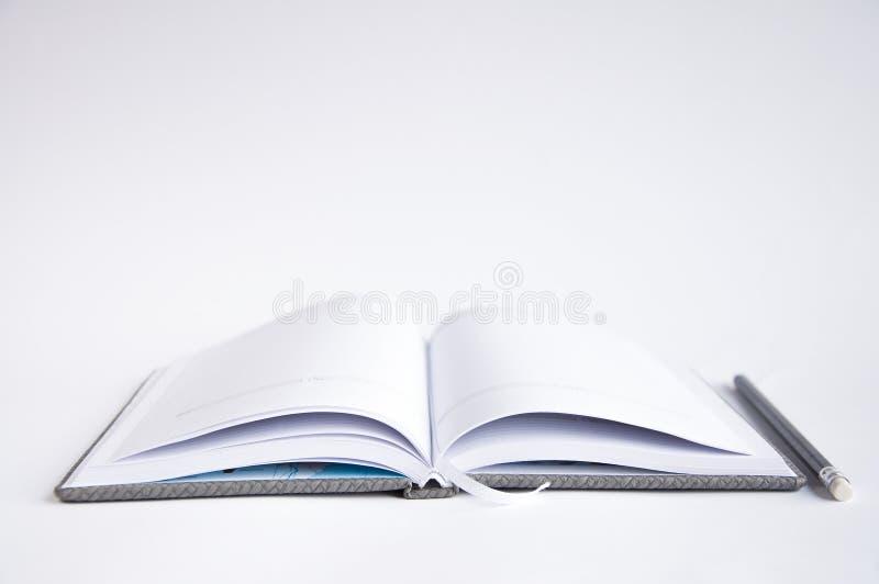 otwarty notatnika st?? Na notatniku jest czarny ołówek obraz royalty free