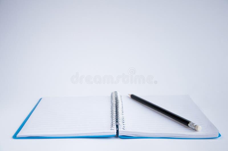 otwarty notatnika st?? Na notatniku jest czarny ołówek zdjęcia royalty free