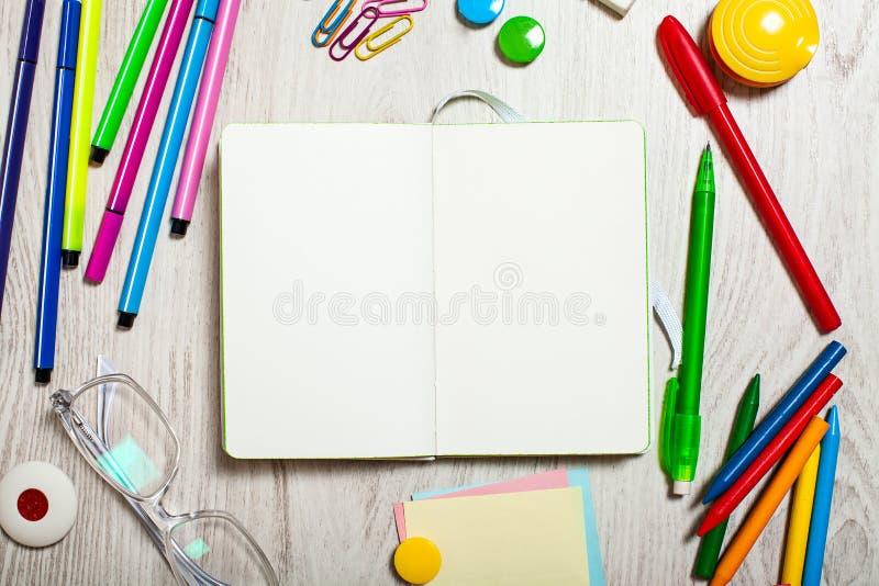 Otwarty notepad z pustymi stronami na stole z biurowymi narzędziami zdjęcia royalty free