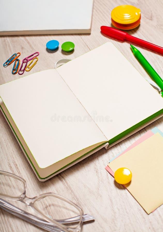 Otwarty notepad z pustymi stronami na stole z biurowymi narzędziami zdjęcie stock