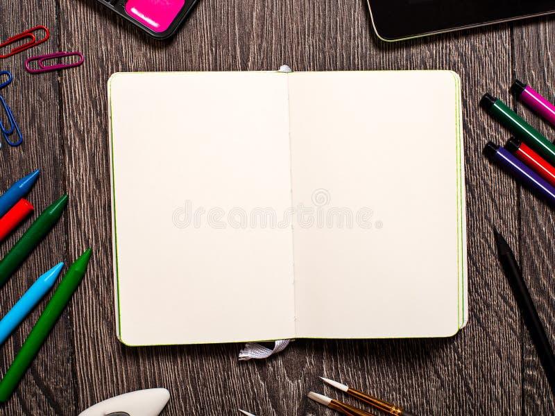 Otwarty notepad z pustymi stronami na stole z biurowymi narzędziami obrazy stock