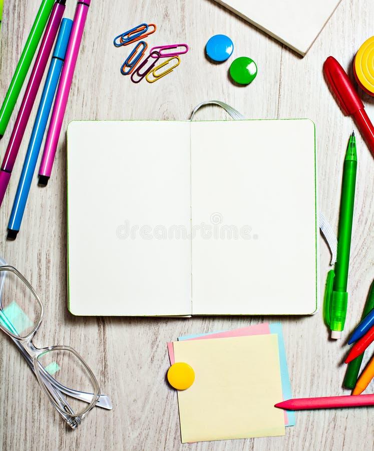 Otwarty notepad z pustymi stronami na stole z biurowymi narzędziami zdjęcia stock