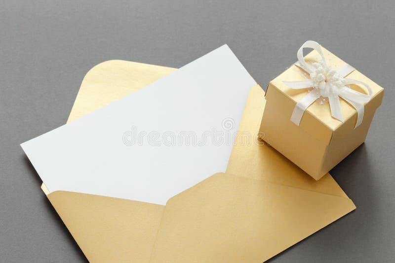 Otwarty papierowy kopertowy złoty kolor z pustego papieru prześcieradłem i prezenta pudełkiem z faborkiem na szarym tle obraz royalty free