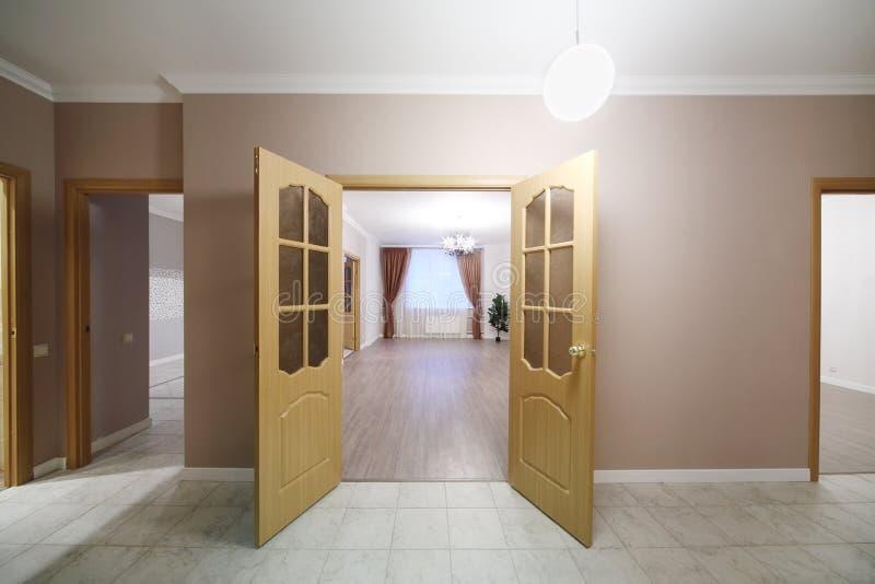 Otwiera drewnianych drzwi prowadzi w przestronnego pokój obrazy royalty free