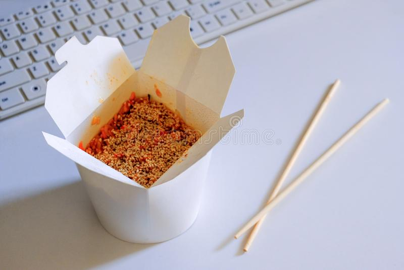 Otwiera karton z Azjatyckim jedzeniem dla programisty Rice z owoce morza, sezamowymi ziarna i chopsticks na biuro stole następnie zdjęcie stock