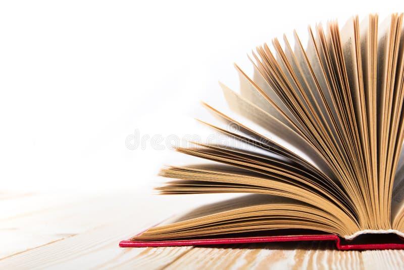 Otwiera książkę na drewnianym stole odizolowywającym na białym tle tylna szkoły kosmos kopii fotografia stock