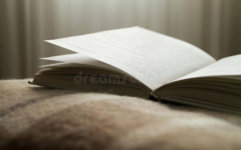 Otwiera książkę na koc na naprzeciw okno, obrazy stock