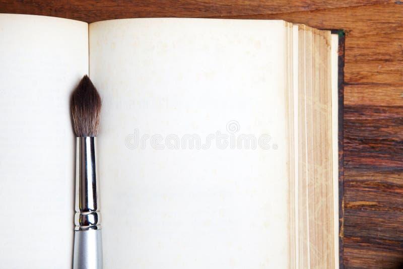 Otwiera książkę z farby muśnięciem. fotografia stock
