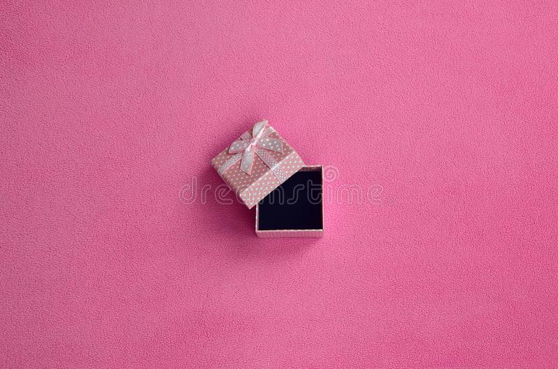 Otwiera małego prezenta pudełko w menchiach z łęku małymi kłamstwami na koc miękki i owłosiony światło - różowa runo tkanina Pako obrazy royalty free