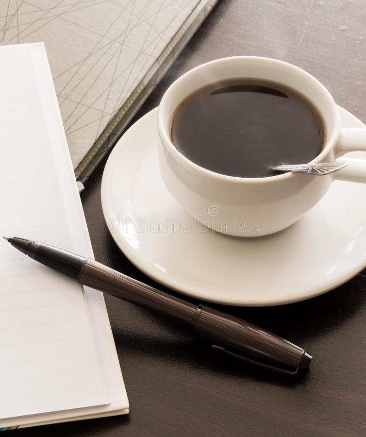 Otwiera notatnika, pióro i filiżankę kawy pustych białych, zdjęcie stock