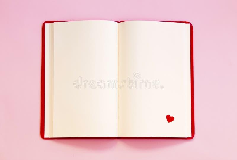 Otwiera notatnika z czerwonym sercem na różowym tle obrazy stock