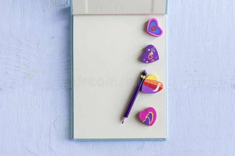 Otwiera notatnika z ołówkowymi i kierowymi gumkami na błękitnym tle, zdjęcia stock