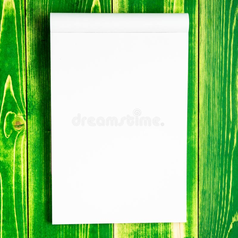 Otwiera notepad dla znaka i nakreślenia na jaskrawym - zielony drewniany tło fotografia stock
