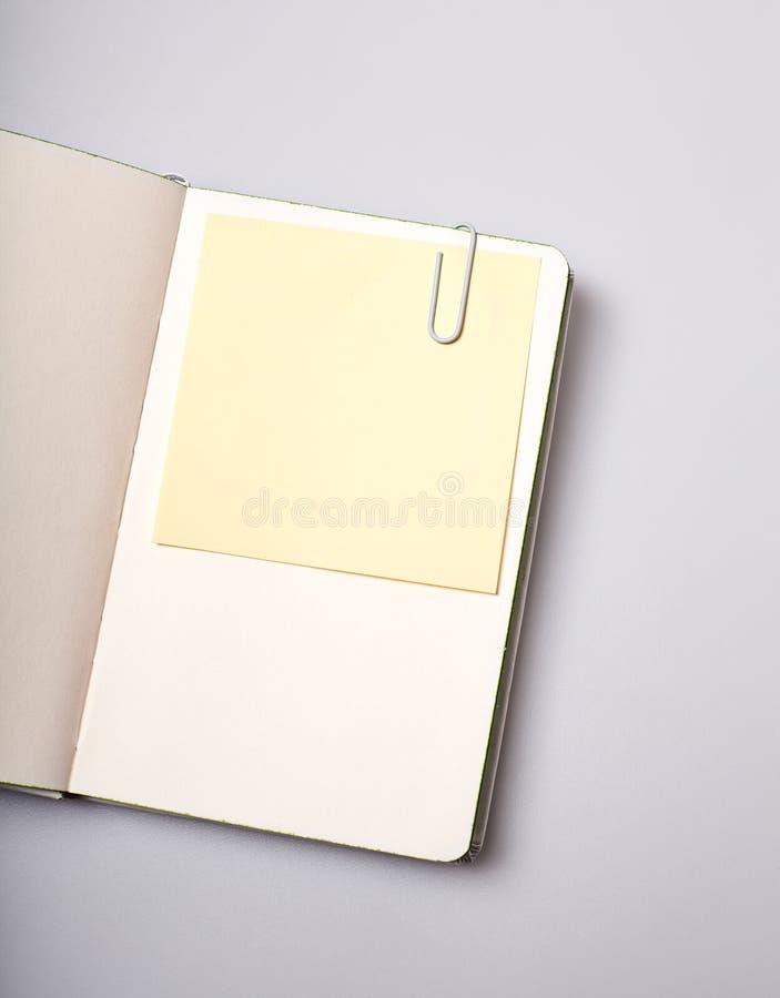 Otwiera notepad pustą stronę z nutowym majcherem na bielu stole fotografia stock