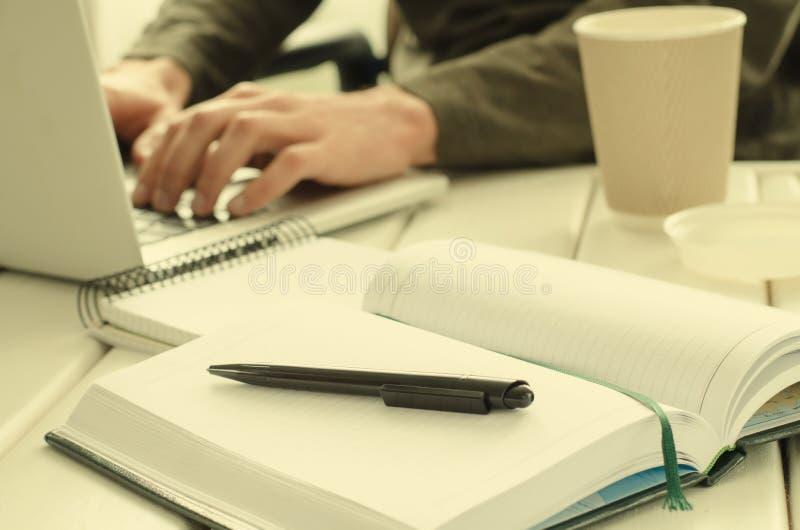 Otwiera notepad z czarnym piórem na stole Papierowa filiżanka kawy, biurowy materiał, laptop i pracujący mężczyzna na tle, obrazy stock