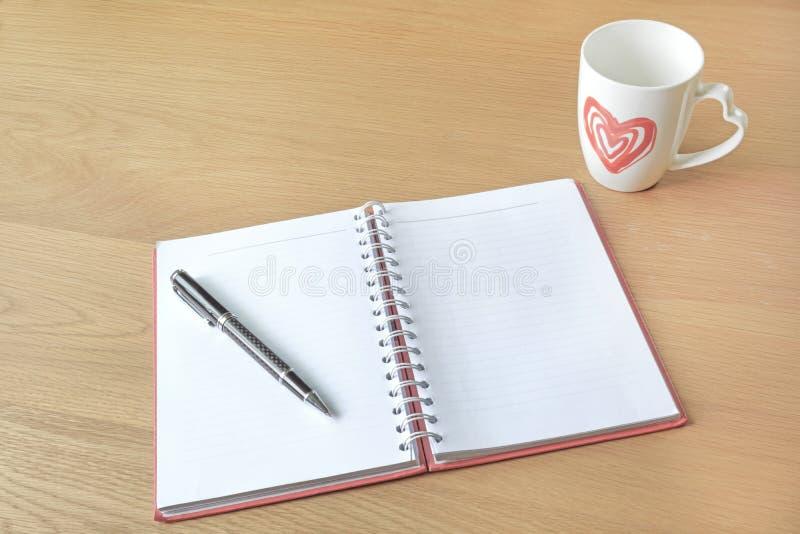 Otwiera pustą białą filiżankę kawy i notatnika obraz royalty free