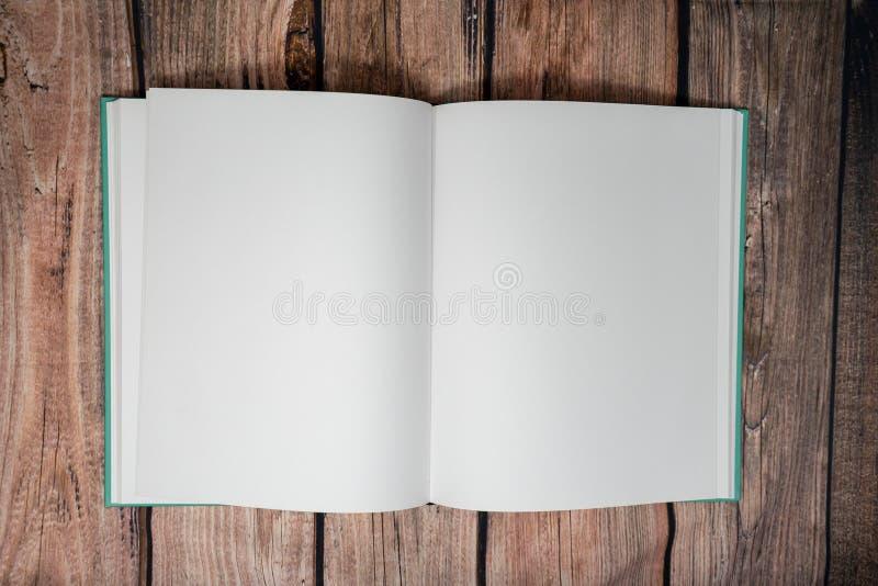 Otwiera pustą papierową książkę i pociska czasopismo bez pisać na stronach nad ciemnym drewnianym tłem, obrazy stock