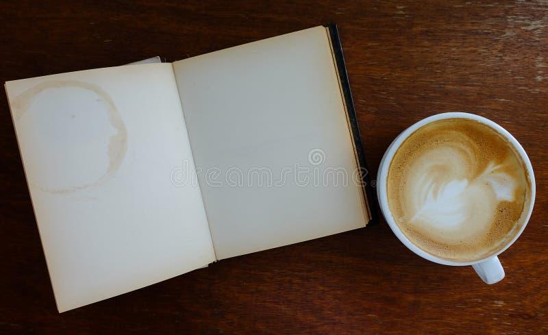 Otwiera pustego starego notatnika na drewnianym stole z gorącą kawą obraz stock
