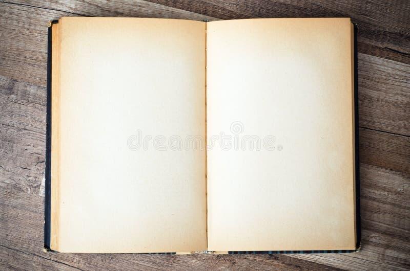 Otwiera starą książkę na drewnianej powierzchni zdjęcie royalty free
