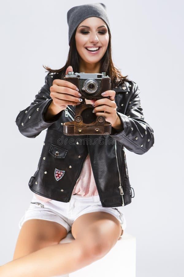 Otwiera Szczęśliwą Kaukaską brunetkę w Czarnej skórzanej kurtce Pozuje Z stara szkoła filmem Photocamera obrazy stock