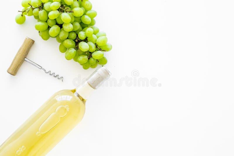 Otwiera wina pojęcie Biały wino w szklanej butelce blisko wiązki winogrona i corkscrew na białego tła odgórnym widoku kopiujemy fotografia stock