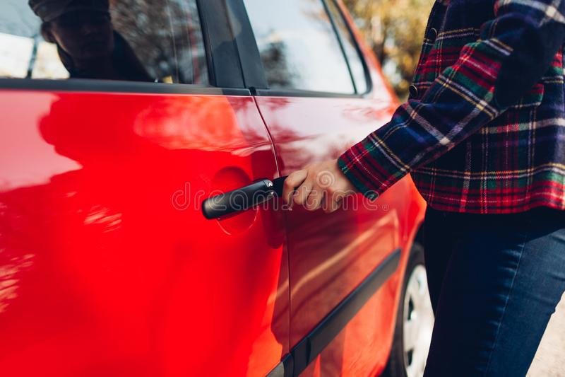 Otwieranie drzwi samochodu Kobieta otwiera czerwony samochód z kluczem fotografia stock