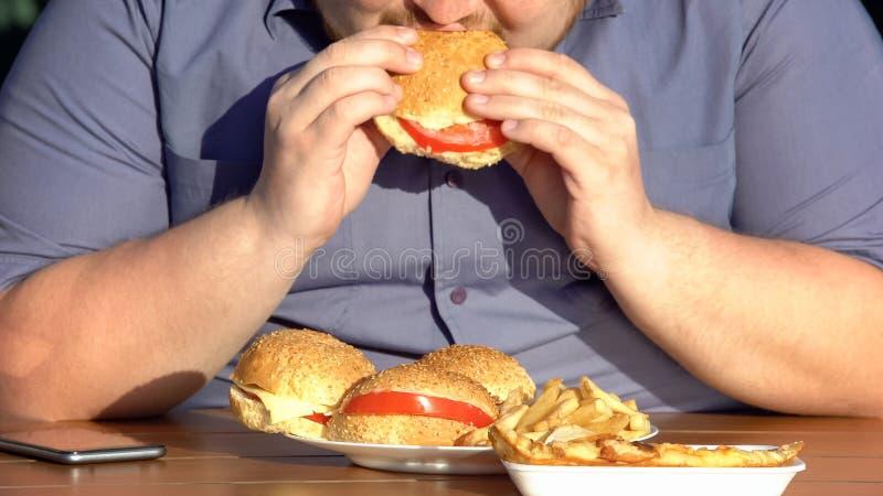 Otyłego głodnego mężczyzna łasowania tłuści hamburgery, niezdrowy karmowy nałóg, nadwaga zdjęcia royalty free