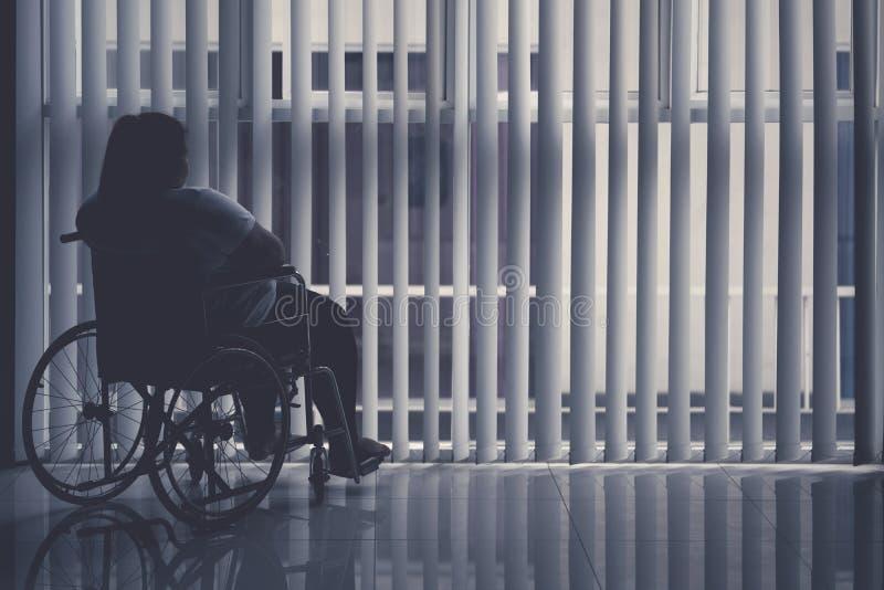Otyła kobieta siedzi w wózku inwalidzkim okno obraz royalty free