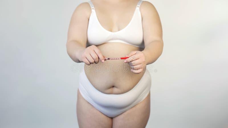 Otyłość konsekwencje, tłuściuchnego kobiety mienia insulinowa strzykawka, cukrzyce mellitus fotografia stock