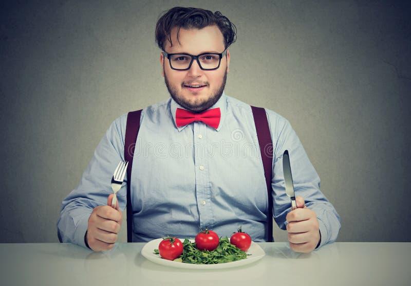Otyły mężczyzna ma zdrowej sałatki na talerzu zdjęcia royalty free