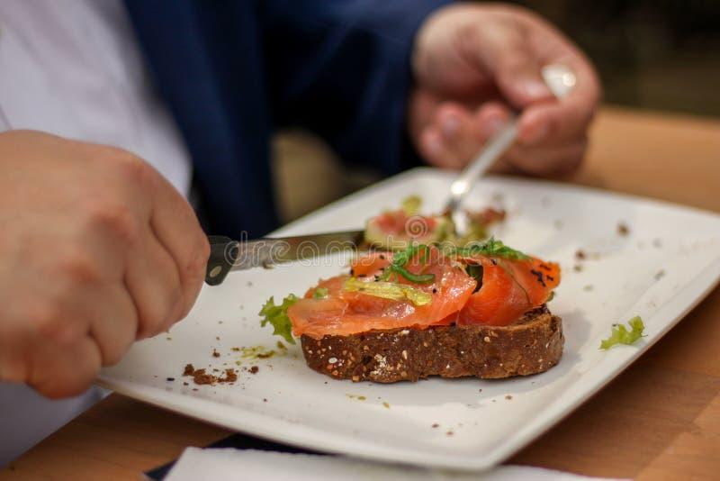 Otyły przy obiadowego stołu łasowania łososiem obraz royalty free