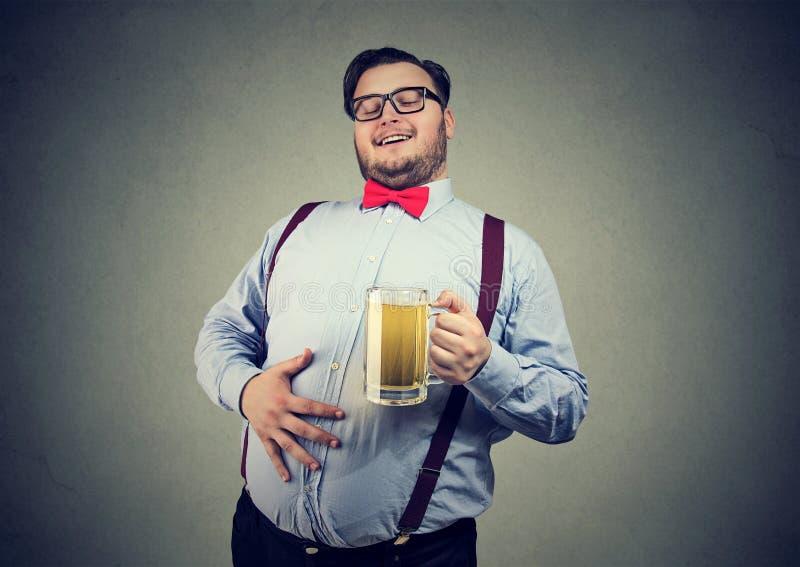 Otyły szczęśliwy młody człowiek folujący z piwem obrazy royalty free