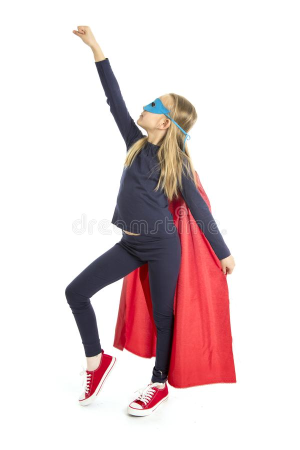 7 ou 8 anos de criança fêmea nova idosa da estudante na execução do traje do super-herói feliz e entusiasmado isolados no fundo b fotografia de stock royalty free