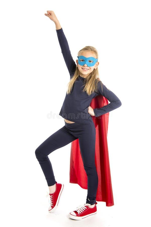 7 ou 8 anos de criança fêmea nova idosa da estudante na execução do traje do super-herói feliz e entusiasmado isolados no fundo b foto de stock