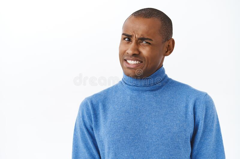 Ouch that hurts. Portrait of embarrassed and awkward young man cringe, grimacing and looking pity camera, feel. Discomfort trying to say something with caution royalty free stock photos