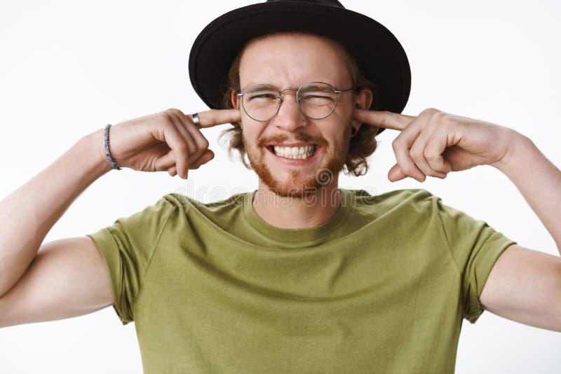 Ouch ruido de disgusto Líder de sexo masculino intenso descontentado de la banda en vidrios y sombrero con la barba y oídos cerra imagen de archivo libre de regalías