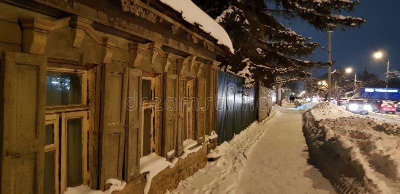 Oud één-verhaal blokhuis op de straat in de winter royalty-vrije stock afbeeldingen