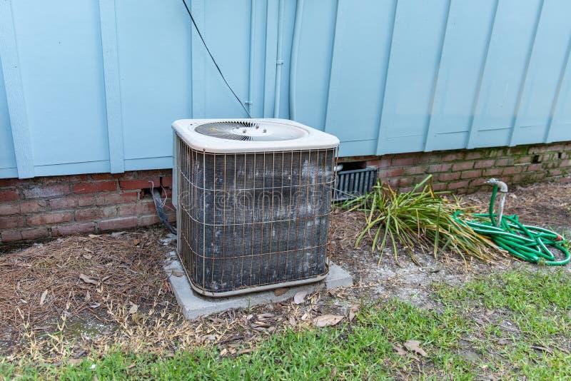Oud airconditionersysteem naast huis met behoefte aan onderhoud royalty-vrije stock afbeelding