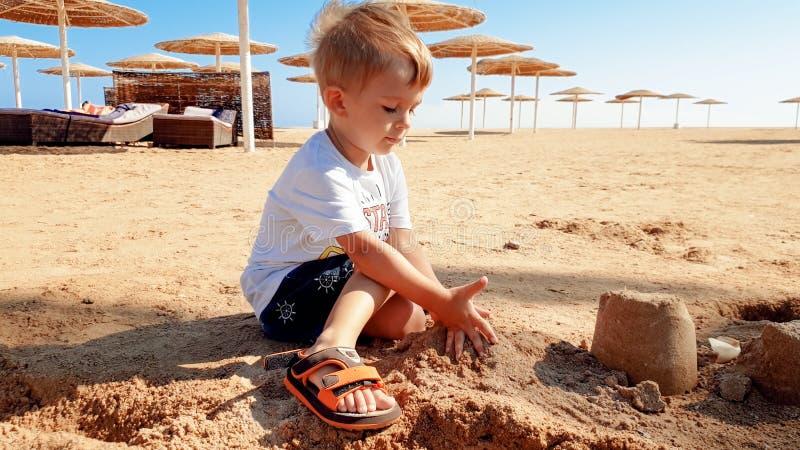 Oud beeld van 3 jaar weinig zitting van de peuterjongen op het overzeese strand en de bouw kasteel van nat zand stock foto