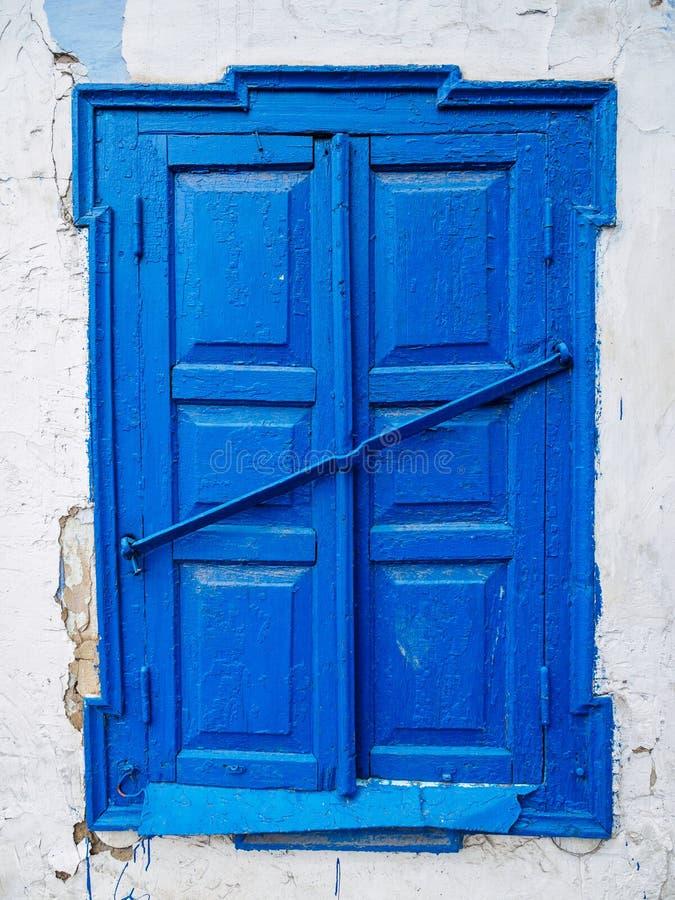 Oud blauw gesloten venster met blinden Geruïneerde muur van een oud huis royalty-vrije stock foto's