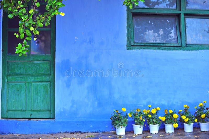 Oud blauw huis met gele bloemen bij de ingang stock fotografie