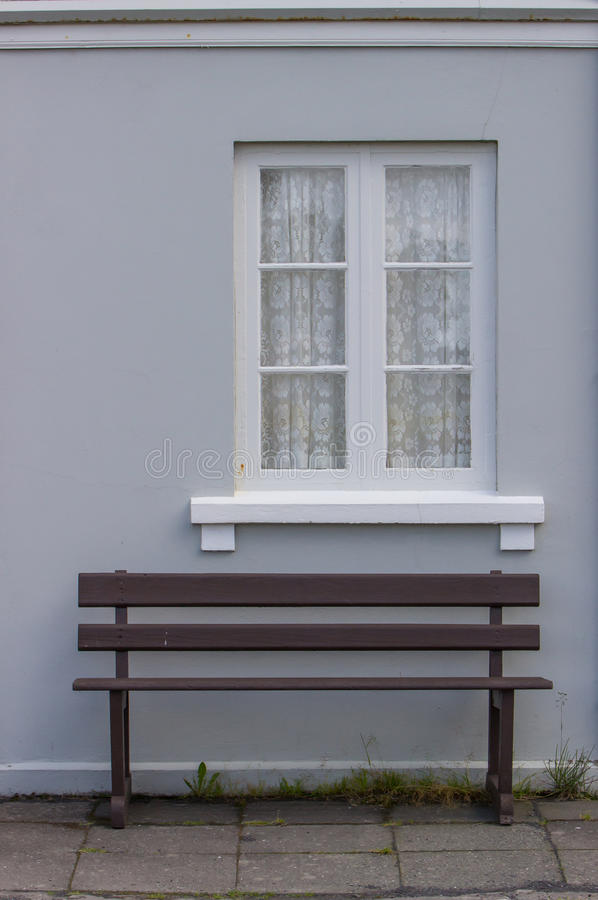 Oud blauw huis met venster en een bank stock fotografie